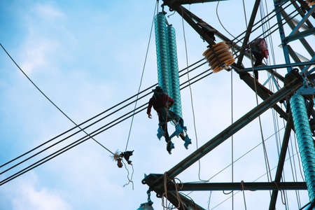 Worker wiring on electric power transmission infrastructure. Electric construction and maintenance services throughout, Electrical power infrastructure security concept.