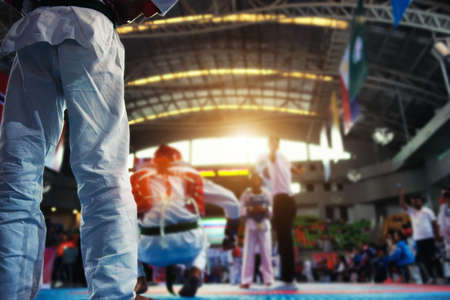 Moment of Taekwondo Kids in the stadiums. Athlete to strike an opponent during the tournament taekwondo kids. Imagens