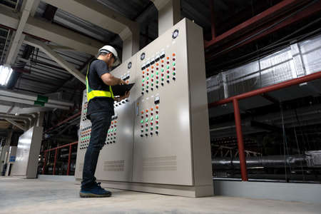 Electrical Engineer team working front HVAC control panels, Technician daily check controls system for security functions in service room at factory. Heating,Ventilation,Air Conditioning.