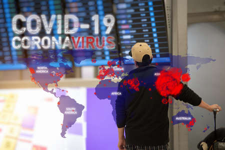 Asian tourist man looking to the Airport Departures while worrying about the Coronavirus disease (COVID-19) outbreak. Tourist protection concept. Global problem background. Imagens