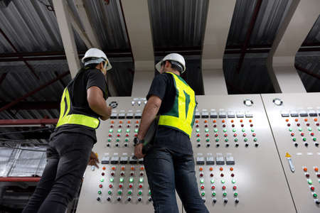 Electrical Engineer team working front HVAC control panels, Technician discussion and training daily check controls system for security functions in service room at factory.