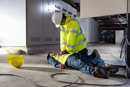 Start Compressions using both hands - 30 times, Life-saving and rescue methods. Accident at work of electrician job or Maintenance worker in the control room of factory. Imagens
