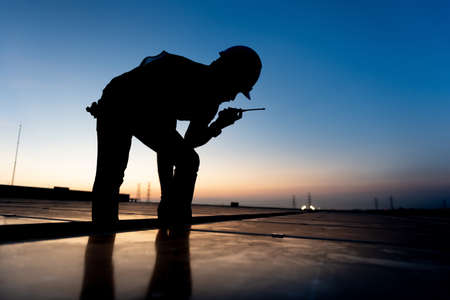 silhouette Technician checking Photovoltaic cells panels on factory roof, Maintenance of the solar panels, Engineer service, Inspecor concept. Silhouette Photo.