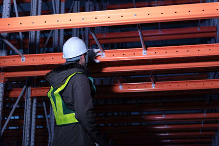 Maintenance technician service in cold warehouse storage, Machinery engineering people checking moving rack system and equipment in warehouse. Imagens
