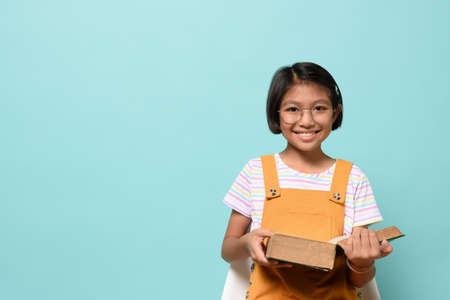 Asian female smile kid wear glasses looking camera and holding dictionary book while sitting chair on pastel blue background in studio. Language Learning of Schoolgirl, learning by heart concept.