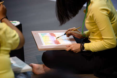 Activities for painting watercolor on paper drawing of students in spacious studio.