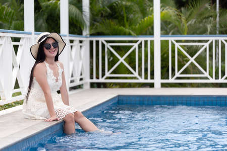 Young woman sitting relaxed in the pool at the garden in hotel on the background.