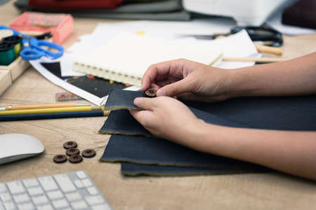 Hands of female tailor while compare the shirt buttons for maching fabric on table at cutting dressmaker studio, Cutting and design concept. Very shallow focus point at shirt buttons. Imagens