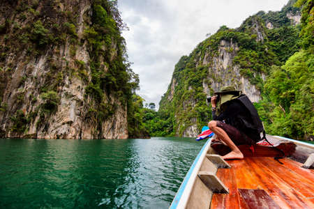 Man traveler photograph relaxing and floating in a boat on the asia lake or among the islands with mountains in background