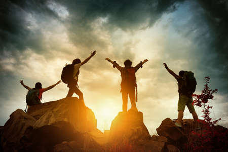 Celebrating life of Hikers climbing up mountain cliff. Climbing group helping each other while climbing up in sunset. Concept of help and teamwork, Limits of life and Hiking success full. Editorial