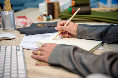 Close-up Hands of female fashion designer or tailor while startup drawing on daily book in cutting and design studio of dressmaker. Very shallow focus point at her hand while note.