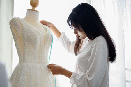 Tailor or Designer woman's taking measurements the wedding dress with measuring tape at cutting and design studio. Very shallow focus point at her hand-in job
