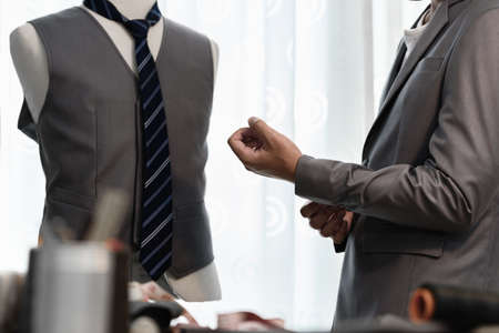 Man wearing suit after sewing suit at tailors shop. Custom made cloth. Focus point at his hand while buttoning up. Imagens