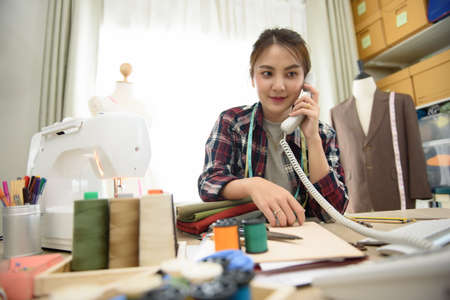 Asian young woman fashion designer call to customer or partners in job small business in cutting studio having a sewing machine and other equipment on desk, Design business freelance concept.