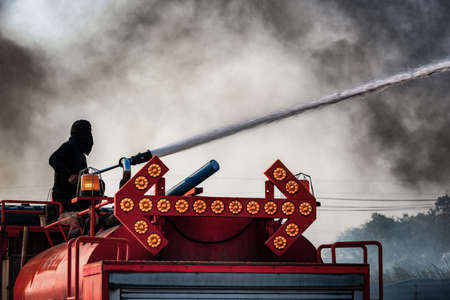 Fireman extinguishes a landfill  in harsh conditions of fire, flames and smoke while on the on fire engine 免版税图像