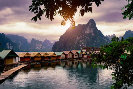 Raft house homestay at lake river in natural attractions with beautiful sunset and mountain scenery background at Ratchaprapha Dam at Khao Sok National Park, Surat Thani Province in Thailand.