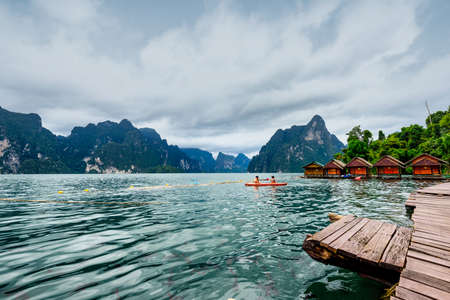 Enjoying relax trip with Red canoe on the Asia lake and Raft house homestay in the among the islands with mountains in background at Surat Thani Province of Thailand.