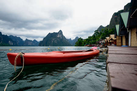 Red canoe floating on the Asia lake and Raft house homestay in the among the islands with mountains in background.