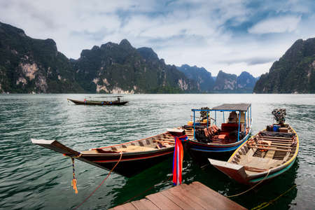 Long-tailed boat group floating on the asia lake in the among the islands with mountains in background at Surat Thani Province of Thailand. Imagens