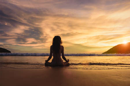 Silhouette of young woman wearing a bikini practicing yoga on the beach at sunset with around sea beach ocean, Yoga Meditation Sunset on the beach alone, Mindfulness Meditation for health.