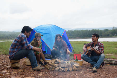 Happy friends camping party playing music and enjoying bonfire in nature and lake, Partying in camping, Asian Young people celebrating,  travel activity concepts Фото со стока