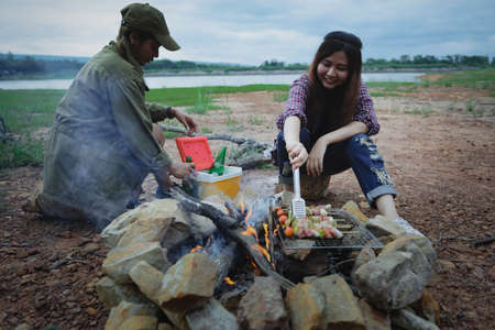 Happy friends camping enjoying bonfire in nature, Partying in camping, Asian young women people celebrating during vacation, Summertime and travel activity. Фото со стока