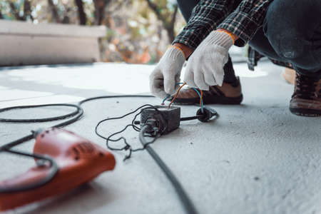 Hand connecting power outlet to an electric tool no electrical plug cause electric shock, Be unaware of worker,  Work accidents electric shock of a worker in the workplace concept.