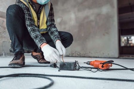 Hand connecting power outlet to an electric tool no electrical plug cause electric shock, Be unaware of worker,  Work accidents electric shock in the workplace, Selection focus shooting on his hand. 免版税图像