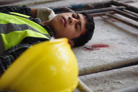 Teenager worker with trauma of the head, Work accident head broke at the construction site and Lying unconscious on the floor.