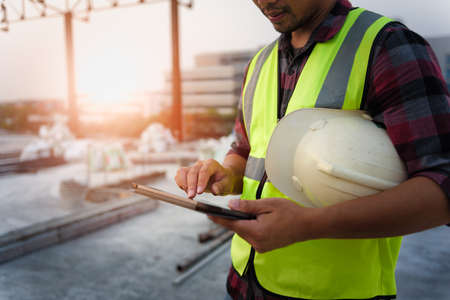 Engineering Consulting People on construction site holding tablet in his hand. Management in business workflow and Building inspector with BIM technology in Construction Project. Фото со стока