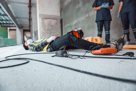 Work accident electric shock to a worker in the workplace and Unconscious lying on the floor after hand connecting power outlet to an electric tool no electrical plug.