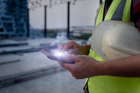 Engineering Consulting People on construction site holding tablet in his hand. Management in business workflow and Building inspector with BIM technology in Construction Project. 免版税图像