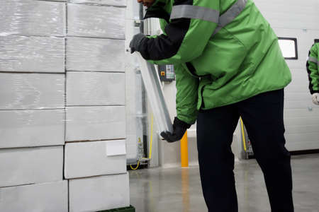Plastic wrapper roll to packaging in loading goods of the freezing warehouse., Storage for Coronavirus Vaccine in cold room., Export-Import Logistics system concept. Focus shooting on package box.