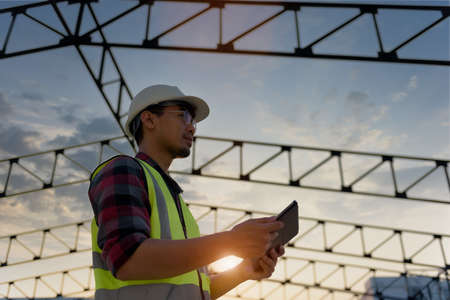 Engineering Consulting People on construction site holding tablet in his hand. Management in business workflow and Building inspector with BIM technology in construction project while sunset.
