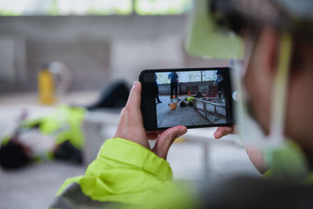 Smartphone shooting on accidents and Unconscious of worker in workplace at construction site area while having the Medical assistance first aid team with equipment. Фото со стока