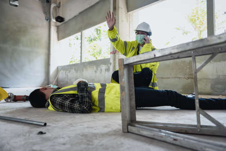 Work accidents of worker in workplace at construction site area and Unconscious with colleague motion and call to the safety officer for rescue and Life-saving. Selection focus on an Injured person.