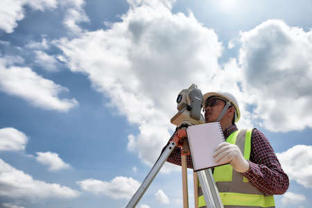 Construction Surveyors distance measurement with cloud sky background, Surveying outdoor for making layout plans is a graphical representation of the lay of the land startup construction work.