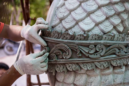 Close-up hand of Myanmar skilled artisan while using mortar concrete making a large great naga statue.