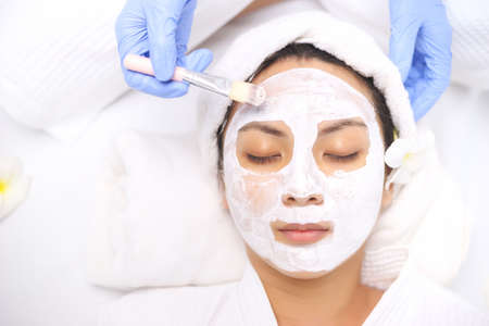 Young Asian Women getting facial care, Facial masks, and spa beauty treatment for soft smooth silky skin by beauticians at spa salon. Beauty skincare concept