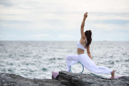 Young woman exercise yoga in nature sky & sea view. Easy yoga poses for beginners with Yoga Wheel in evening, Stretching & Strengthening Exercises with advanced yoga, Relaxation & Health care concept.