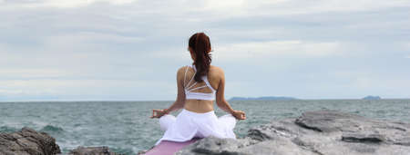Asian young woman practicing yoga in sukhasana exercise while looking out to the sea. Banner size with copy space. Banque d'images