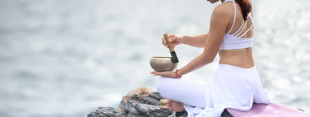 Asian young woman practicing yoga while sitting on nature sea rock. Easy yoga poses for beginners. Exercise while looking out to the sea. Meditation with yoga. Banner size with copy space.