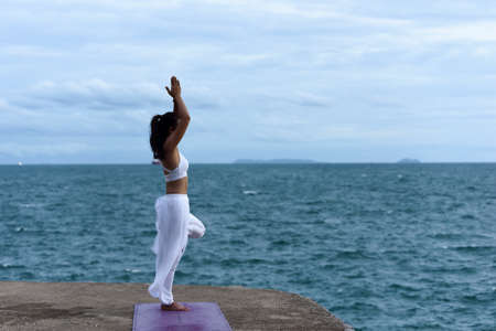 Asian young woman practicing yoga with sea view. Easy yoga poses for beginners. Exercise while looking out to the sea. Stretching and Strengthening Exercises with yoga.