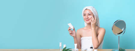 Beautiful Asian young woman smiling while applying white cream on her face with many packaging of facial cream and cosmetics on wooden table. Banner size with copy space light blue background. Banque d'images