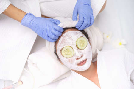 Young Asian Women getting facial care, Facial masks, and spa beauty treatment for soft smooth silky skin. Helps with homemade apply face mask with cucumber slices eyes mask for Tired Eyes.