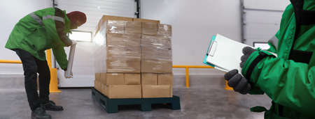 Staff wrapping film packaging boxes with a note at   warehouse in banner, Loading goods prepare storage in the freezing room, Warehouse Storage System Service in Logistics Business concept