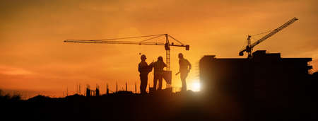 Silhouette engineer construction work control and tower crane background on natural sunset sky.,Heavy industry and building construction work concept in banner