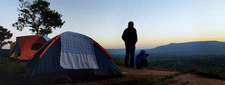 People wake up looking at mountain view in background before sunrise near camping tent. Relaxing activities camping in forest or mountain park.