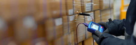 Hand of worker using thermometer to temperature measurement in the goods boxes with ready meals after import in the cold room or warehouse for keep temperature room, Logistics Banner with copy space
