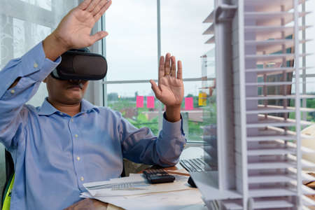 Engineer or Architects wearing virtual reality headsets for work with virtual reality modeling software application. Use Virtual Reality  Modeling and BIM Technology in the Building complete.